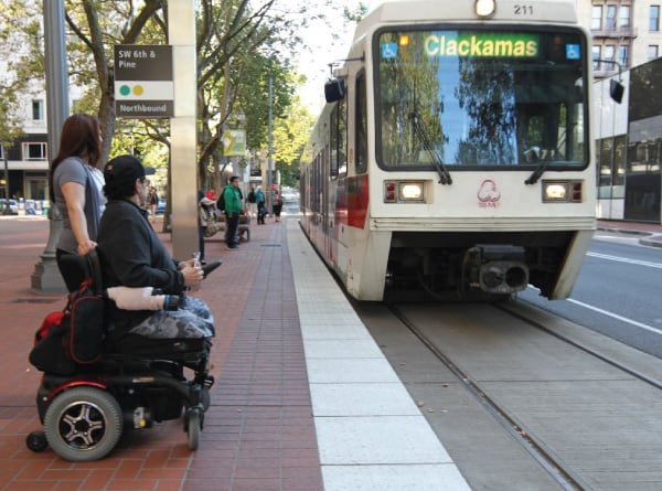 A TriMet light rail pulls up as an MTM Transit assessment evaluator and a man who utilizes a wheelchair looks on. MTM Transit helps TriMet ensure LIFT paratransit eligibility.