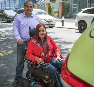 A driver stands behind a woman who utilizes a wheelchair. On behalf of the TLC's Accessible Dispatch program, MTM dispatches accessible taxis to New Yorkers with disabilities.