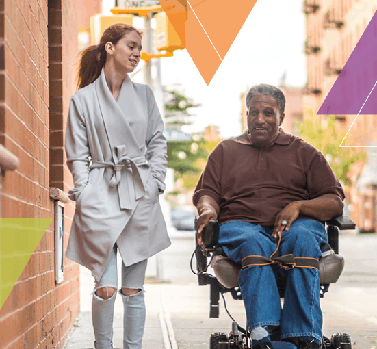 A travel trainer and a person who utilizes a wheelchair venture down a sidewalk after an ADA eligibility assessment for ADA certification. MTM Transit eligibility assessments and travel training through mobility management help people learn how to use public transit.