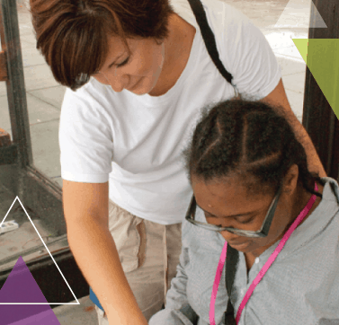 A woman stands behind another woman. Using MTM Transit eligibility assessments for ADA certification, she is helping the woman learn how to use public transit through our mobility management, ADA eligibility assessments, and travel training methods.
