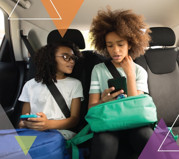Two young girls look at their phones while sitting in a vehicle. MTM Transit offers reliable student transportation and special needs transportation to schools and programs serving children, including those covered by the McKinney-Vento Act.