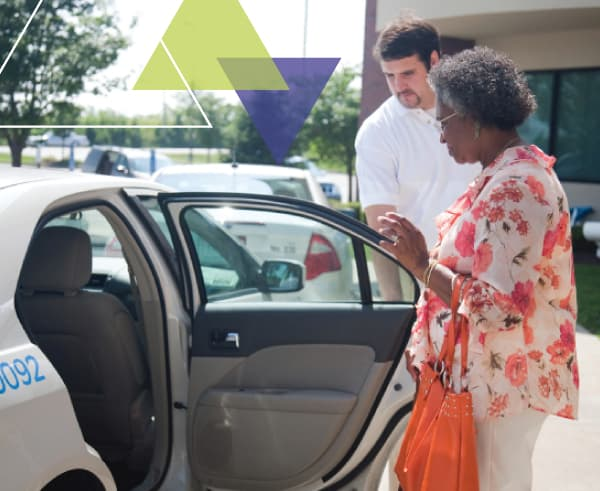 A driver helps a woman into his vehicle. MTM Transit's ADA paratransit brokerage approach leverages the brokerage model to increase the efficiency of paratransit fleets.