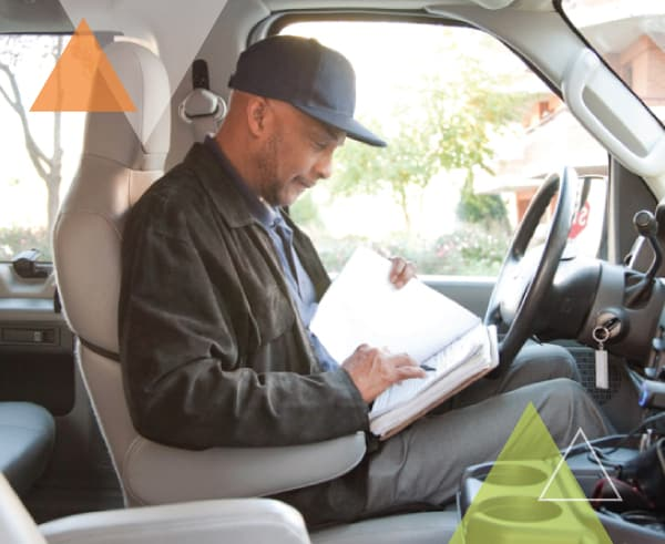 A man sits behind the wheel of his vehicle looking through the trip manifest. MTM Transit offers our clients with paratransit fleets our ADA paratransit brokerage approach and brokerage model.