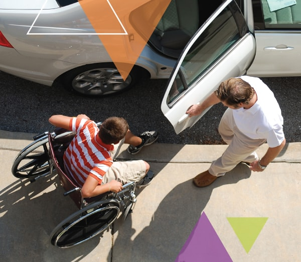 An MTM Transit driver helps a man who utilizes a wheelchair in to his vehicle. While solving our clients' transit challenges, we ensure every trip is important.